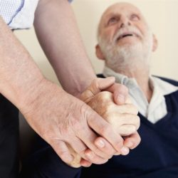 Caregiver holding hand of client
